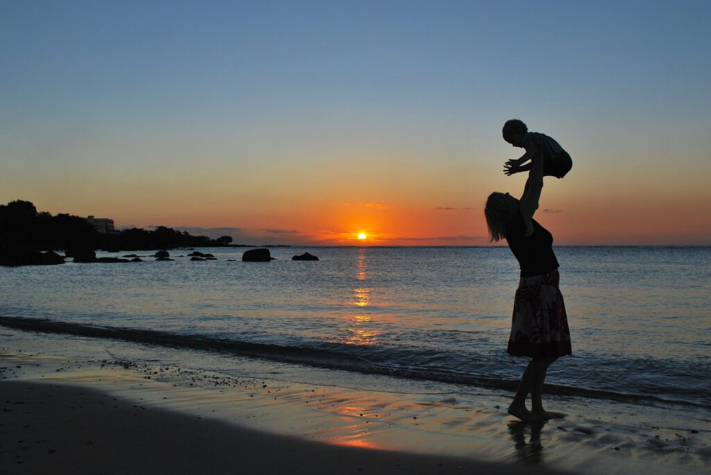 mom and baby on a sunset beach