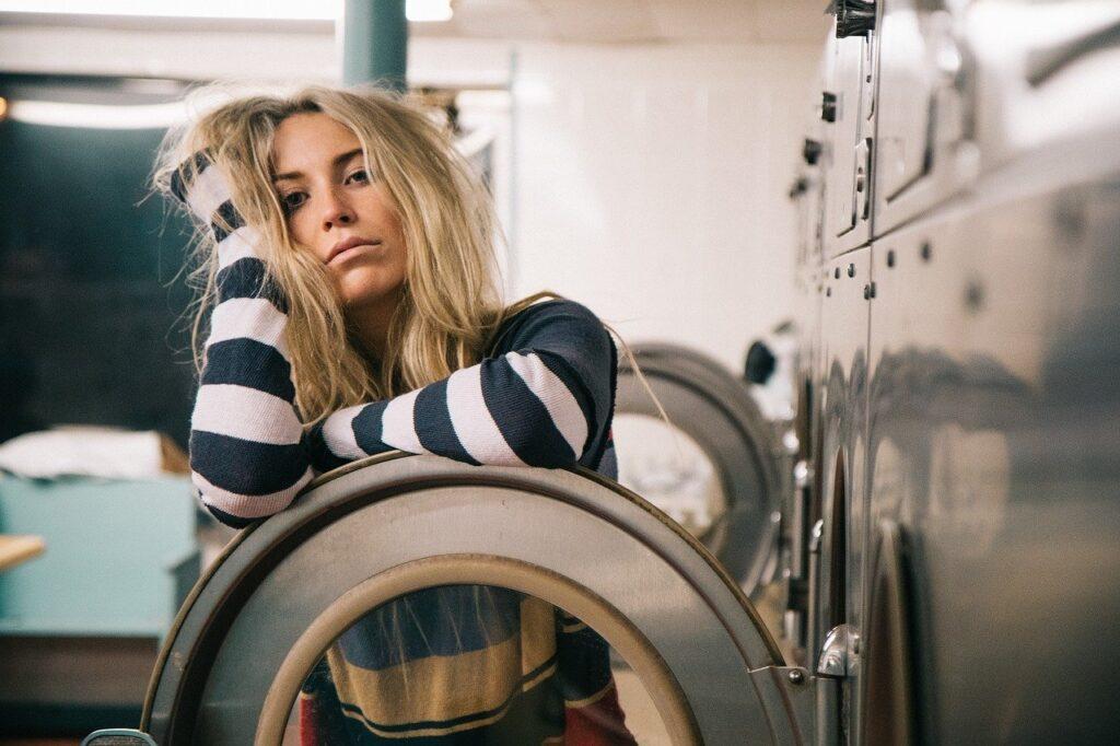 frazzled woman standing behind washer door