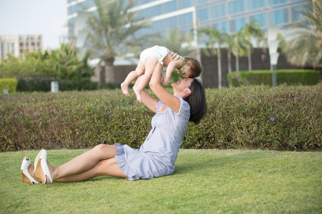 Mother lifting baby in air outside